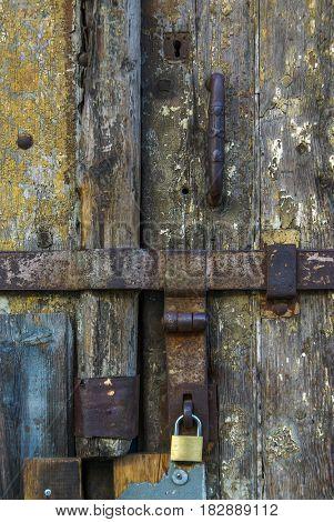 Detail of rusty metallic locks and padlock on an old wooden door