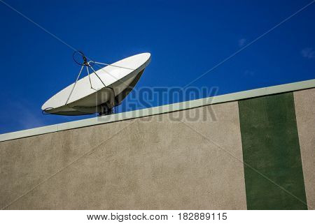 A disc antenna on the roof of a building capturing satellite signal