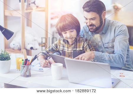 Father and son time. Young father helping his son with homework and looking at a digital table while sitting at a writing table
