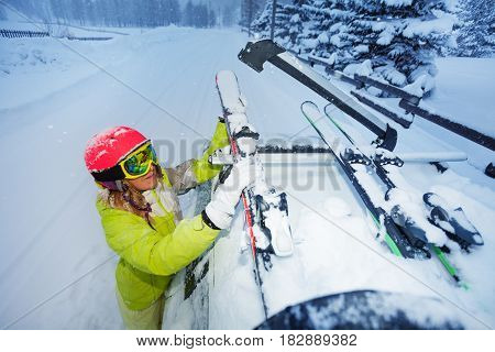 Top view portrait of female skier fastening skis to roof rails of the car after ski trip in the evening
