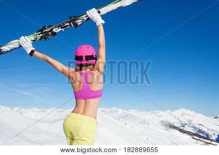Close-up picture of sporty female skier with skies in outstretched arms above head against of snowy mountains, back view
