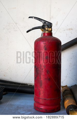 The old fire extinguisher stands on the shelf