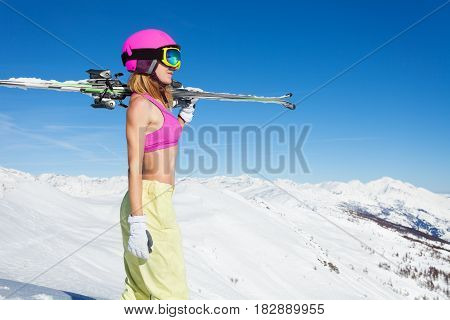 Side view portrait of active woman wearing sports bra in good shape standing with skies on her shoulders on the slope