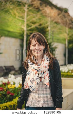 Young Smiling Happy Girl In Pink Shirt, Black Jacket And Anchors Scarf Looking At Camera Outdoors. P