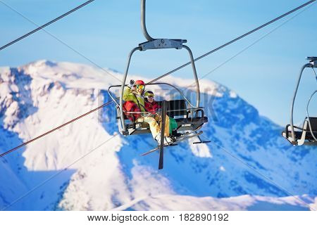 Portrait of happy young woman and her son lifting on chairlift against snowy mountains