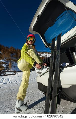 Full-length portrait of happy female skier putting her ski boots on, standing next to the car trunk