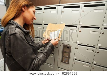 Close-up portrait of smiling young woman holding envelopes with copy-space, standing next to the mailboxes