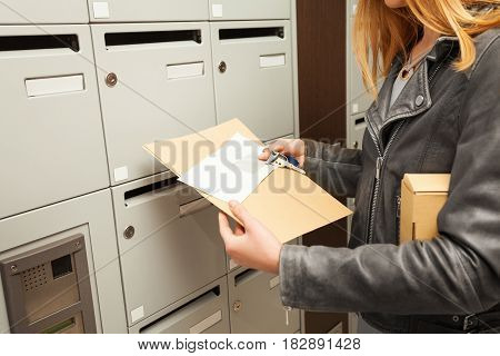 Close-up picture of woman's hands holding envelopes and package next to the mailboxes