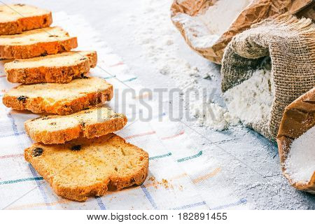 Homemade cake slices next to packs of flour and sugar on the concrete background. Close up