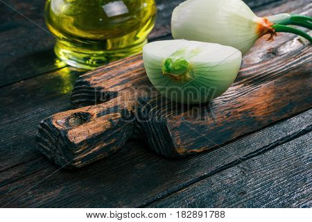 Onion bulbs on rustic wooden cutting board and olive oil in cruet on old dark wood table. Close-up angle view