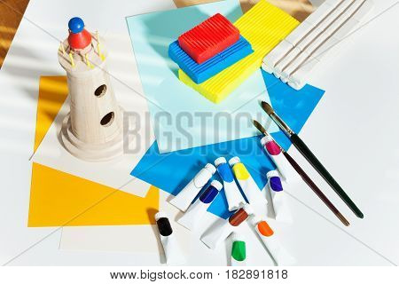 Top view picture of table with brushes, tubes of multicolored paints, modeling clay, color paper sheets and wooden toy tower