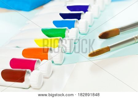 Set of blanked tubes with multicolored oil paint laying in a line on the table