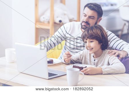 As like as two peas. Riant boy and his dad wearing casual clothes and watching football match at laptop while spending free time in the bosom of their family