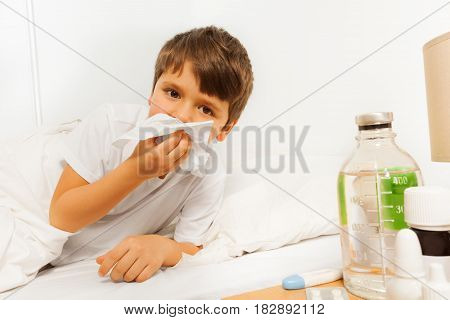 Sick kid boy laying in the bed and blowing his nose with a napkin