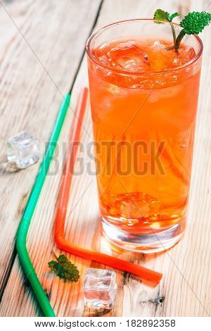 Bright orange refreshing fruit iced drink in high glass and drinking straws on raw wood table