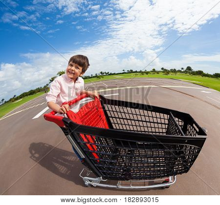 Fisheye picture of happy kid boy playing and riding empty supermarket shopping cart at parking lot