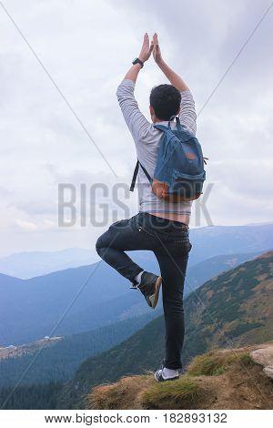 Man standing on edge of mountain, enjoying the beautiful sunset at Carpathians
