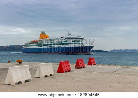 The big sea ferry is moored off in the port of Athinios on the island of Santorini.
