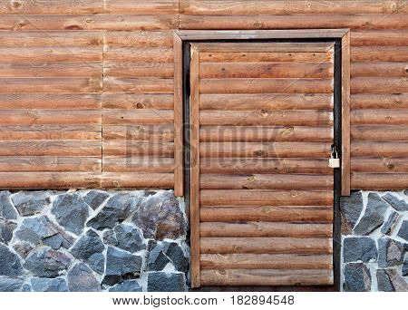 Wooden doors to the back room of the log house and a stone foundation