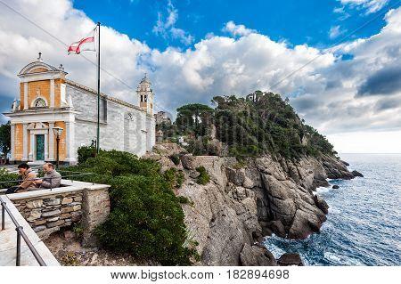 PORTOFINO, ITALY - DECEMBER 2016: Catholic medieval church on the rocks near coastline of mediterranean sea in Portofino town, Italy