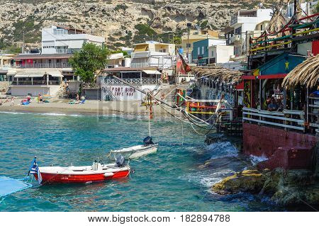 MATALA, GREECE - JUNE 2016: People have a rest at sea bay of Matala town with beautiful beach and taverns around it located on Crete island, Greece
