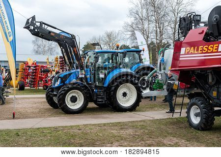 RIGA, LATVIA - APRIL 2017: Blue tractor and other construction equipment at the public event of Riga Machinery Sales.