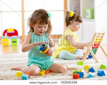 Children toddlers girls play logical toy learning shapes, arithmetic and colors at home or nursery