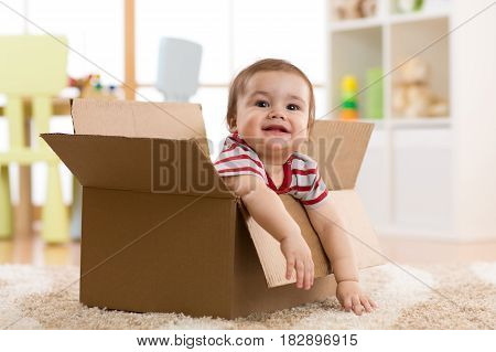 Baby toddler sitting in a carton box