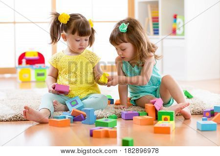 Two friends kids girls play together in kindergarten, daycare or home