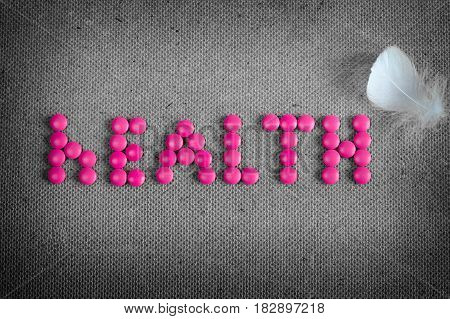 Word health made by pink pills and white feather of bird on the grey background