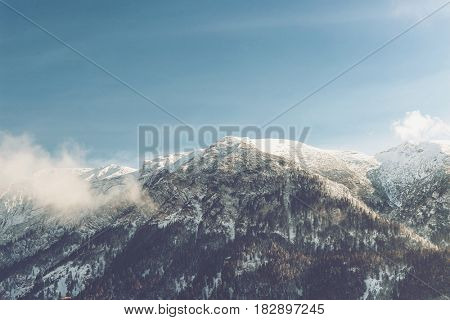 White clouds clinging to a snow-capped mountain summit with forested slopes in a sunny alpine landscape