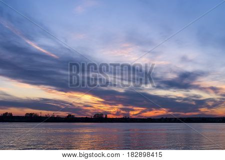 Evening sky in orange colors over the waters of the river