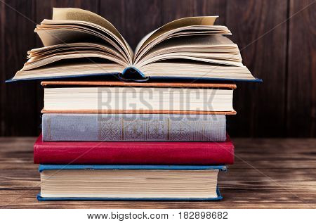 Many old books on wooden background. The source of information. Open book indoor. Home library. Knowledge is power