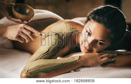 The girl enjoys mud body mask in a spa salon. Focus on the hand with the stick. Luxury treatment.