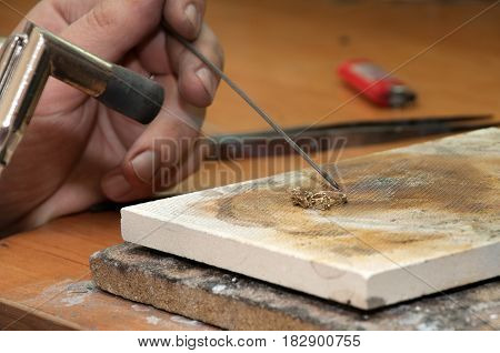 Jeweler processes the workpiece of the ring with a burner
