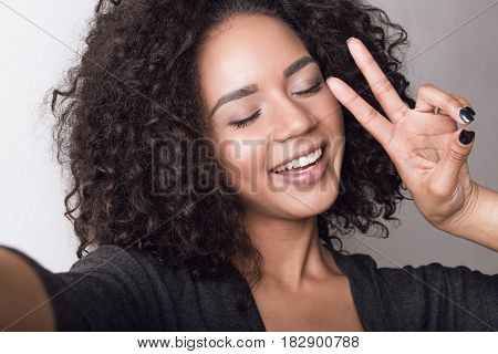 Front view of a happy woman taking a selfie on smartphone and showing peace sign