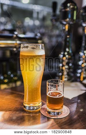 Light beer in a beer glass and dark beer in a small glass lighted with warm light on a wooden bar counter. Vertical frame