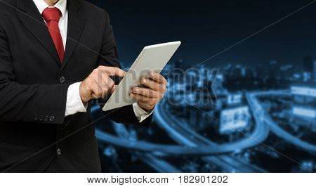 smart businessman in suit using his tablet business and technology concept on blurred night city backgroundcopy space color tone effect.