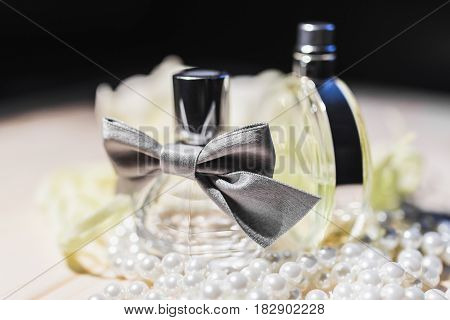 A beautiful bottle of female perfume with a silver bow, a round bottle of light green glass surrounded by pearls stand on a wooden table against a white flower in the dark under the rays of light.