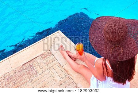 The woman in hat enjoying cocktail in a swimming pool. Vacation and travel concept