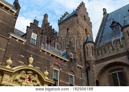 Binnenhof Palace Dutch Parliament The Hague Netherlands. Exterior details close-up : arch with lions turrets on the roof - view from below on sky background