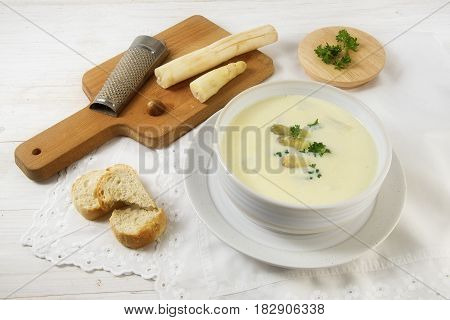Asparagus cream soup with parsley garnish in a bowl and a wooden board with nutmeg grater on a white table soft focus