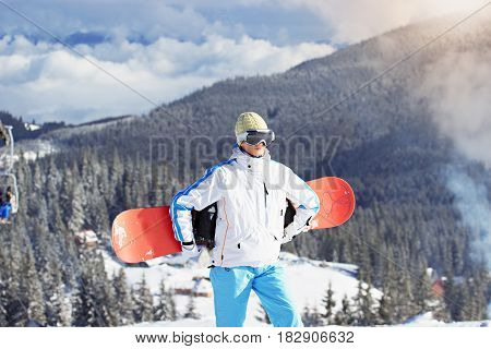 Young Beautiful Girl In White Jacket, Blue Ski Pants And Googles On Her Head Standing With Snowboard
