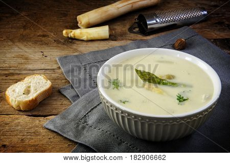 asparagus cream soup with parsley garnish in a bowl nutmeg grater and bread gray napkin on a dark rustic wooden table copy space selected focus narrow depth of field