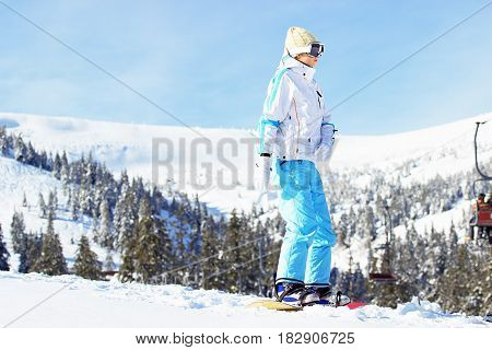 Young Beautiful Girl In White Jacket, Blue Ski Pants And Googles On Her Head Riding On Snowboard In