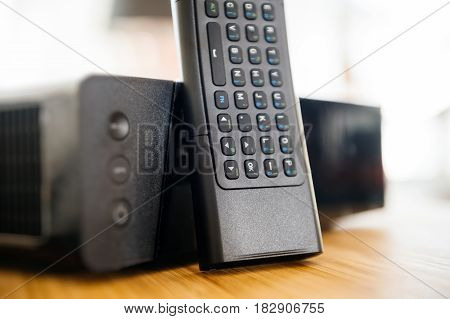 Full keyboard on small remote control next to wireless tv box used for TV Internet Telephone communication via fiber optic or coaxial cable