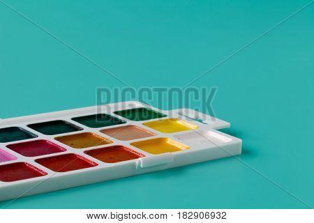 Aquarelle Colors In A Plastic Box On A Aquamarine Background