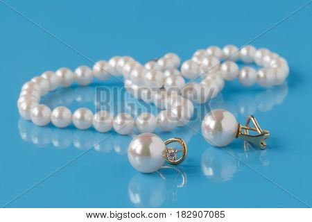Strings of pearl on plain blue background