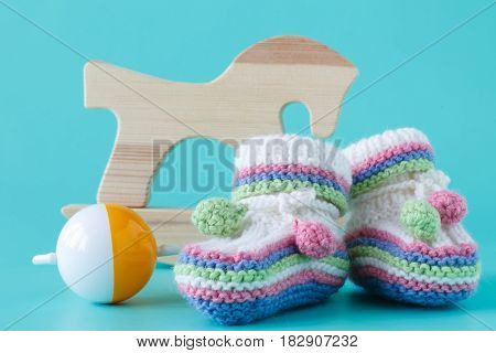 Baby Booties With Baby Rattle Sitting On A Aquamarine Background