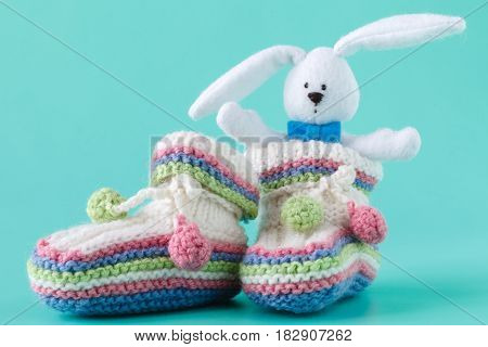 Knitted baby booties with toy on aquamarine background